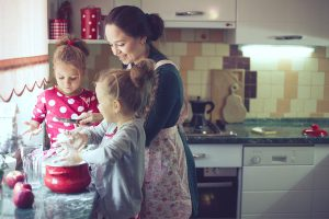 Mother is baking with daughters