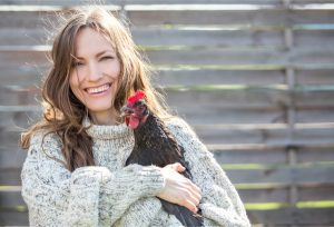 woman holding hen to convey vegan vs plant-based