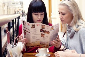 Two women reading menu at a restaurant