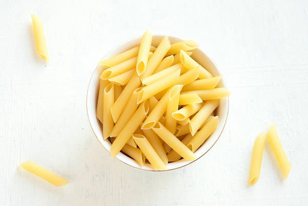 A bowl of pasta penne on a white background.
