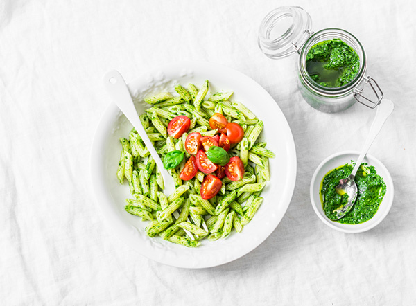 Healthy pasta penne with pesto sauce and cherry tomatoes.