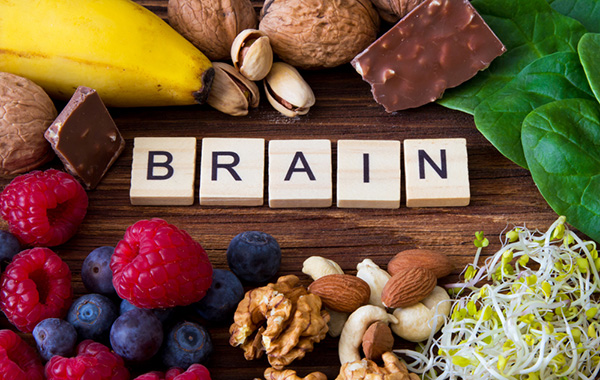 The word Brain written on wooden blocks with foods that improve brain function, health, memory and concentration