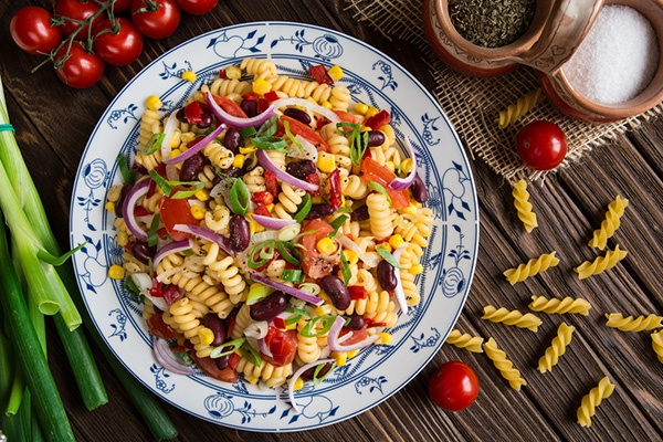 Healthy Mexican macaroni pasta salad with beans, corn, tomato, onion and peppers.