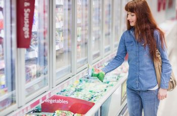 buying vegetables in frozen section in supermarket