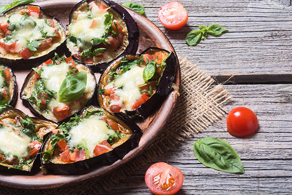 Mini pizza with eggplant , tomato and basil