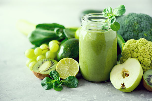 Healthy green smoothie on pale green background