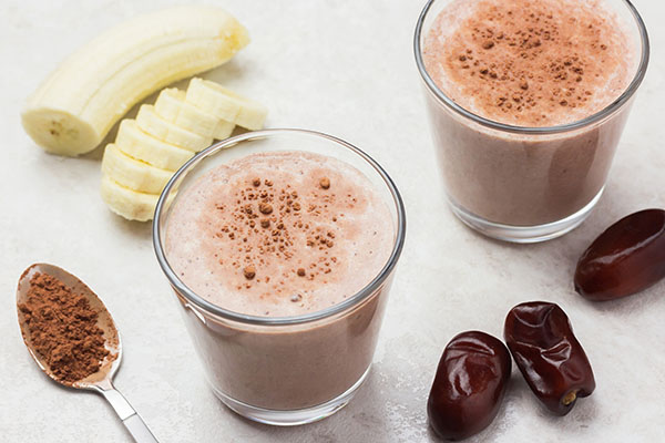 Healthy banana and dates smoothie on cream background.