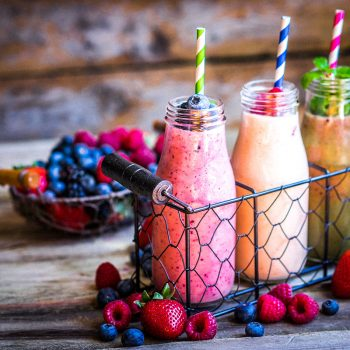 Fruit smoothies on wooden table.